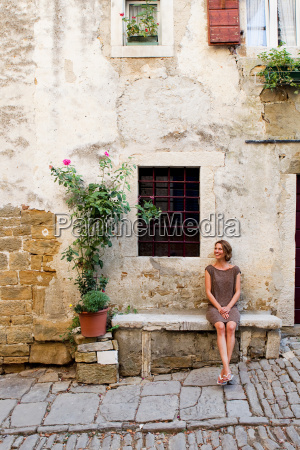 woman outside traditional house groznjan istria