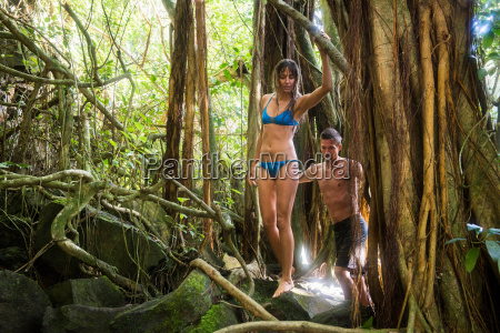 couple climbing tree in jungle