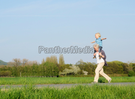 grandmother carrying boy on shoulders