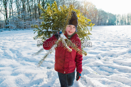 boy carrying christmas tree in snow