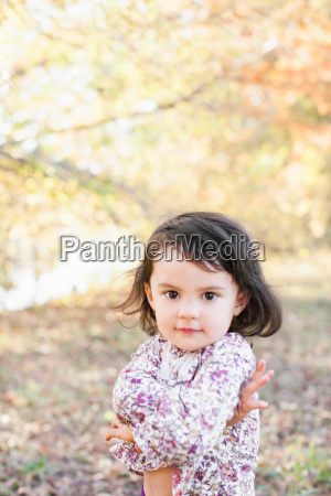child with arms crossed in woods