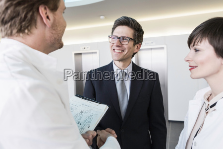 man wearing lab coat holding clipboard