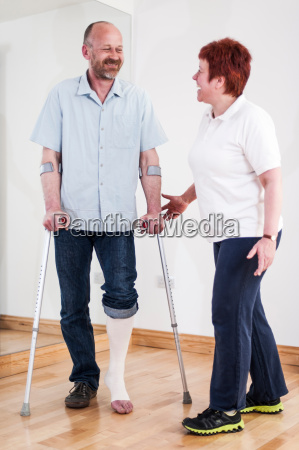 man using crutches talking to woman