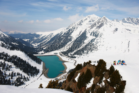skiers in mountain and lake landscape