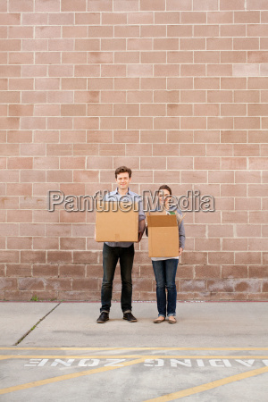 portrait of young couple holding cardboard