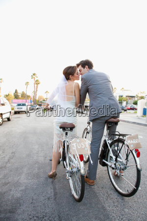 young newlywed couple kissing on bicycles
