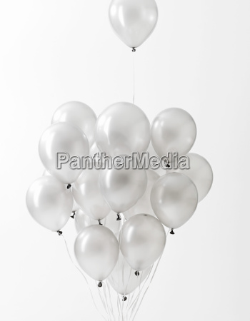 silver balloons floating against white background