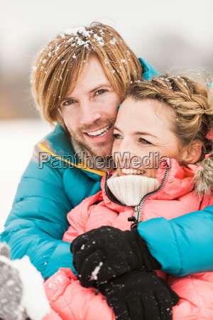 mid adult couple embracing with snow