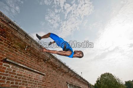 athlete vaulting over brick wall