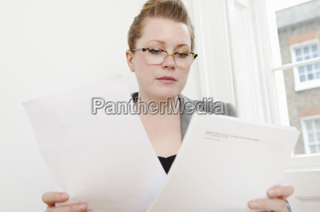 businesswoman reading papers at desk