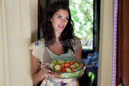 woman holding bowl with salad