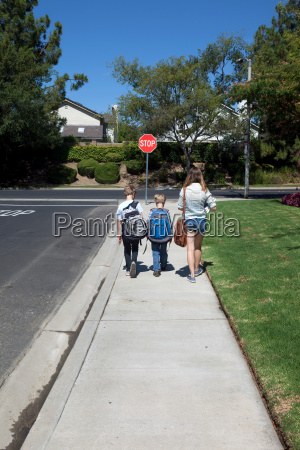 teenage girl walking brothers to school
