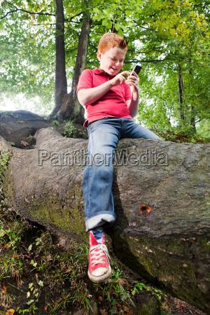 boy sitting on a tree trunk