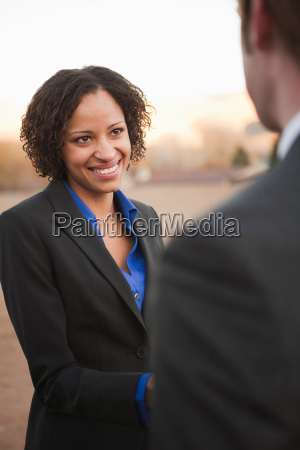 woman in suit shaking hands with
