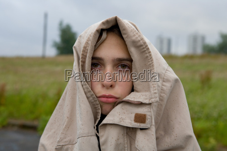 sad looking teenage girl with coat