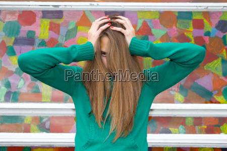 teenage girl with hands in hair