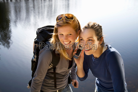 two women outdoors with mobile phone
