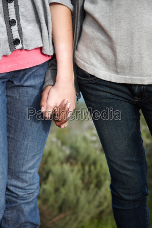 two girls holding hands outdoors