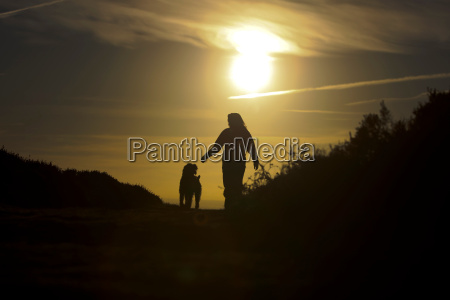 woman walking her dog at sunset