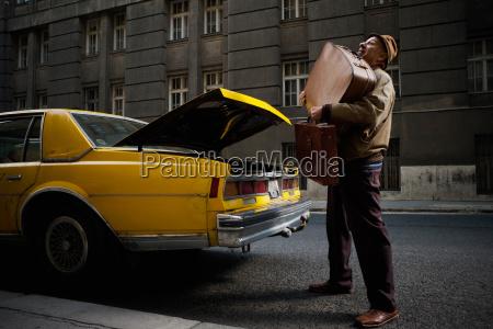 taxifahrer kaempft mit gepaeck
