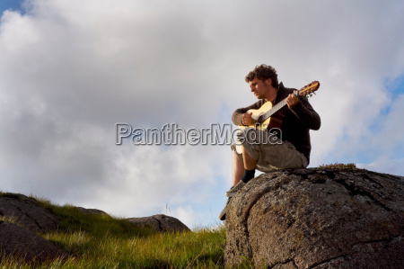 young man playing guitar in landscape