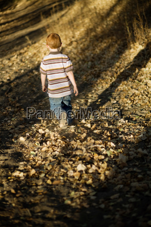 young boy walking in leaves