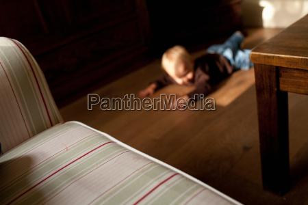 toddler boy lying on floor