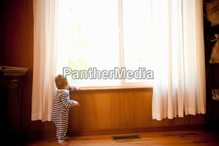 toddler boy looking out of window