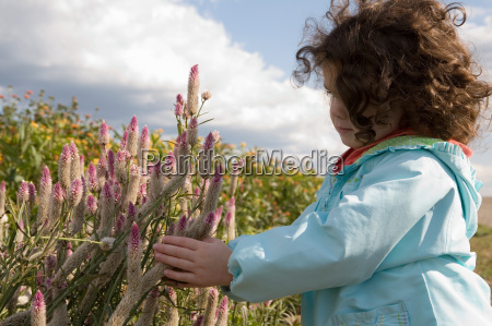 young girl touching wildflowers