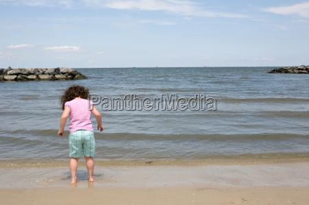 young girl paddling at waters edge