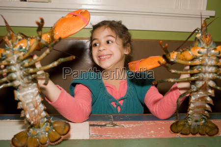 young girl holding two live lobsters