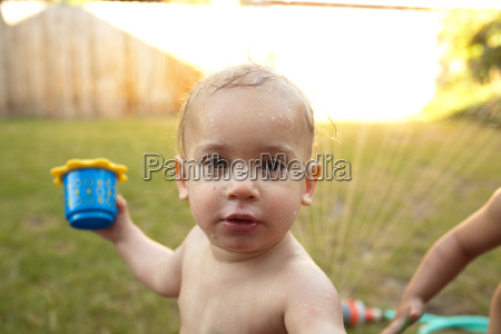 toddler boy playing in sprinkler