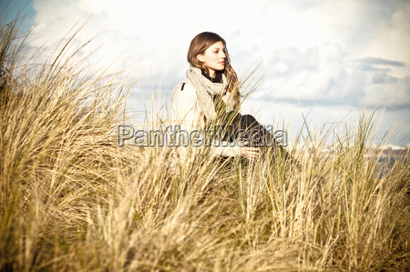 young woman sitting in sand dunes