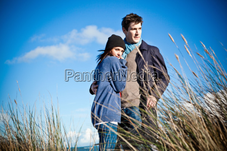 couple standing on sand dunes bournemouth