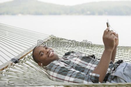 young man lying on hammock listening