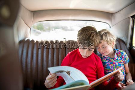 boys sitting in back of car