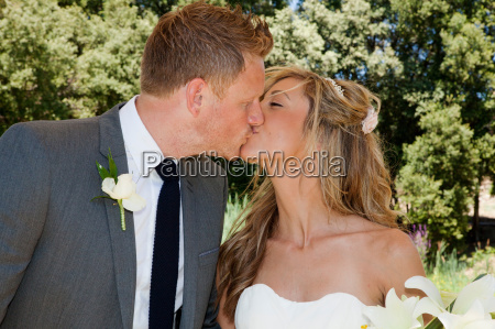 mid adult bride and groom kissing