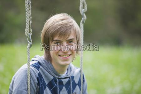 boy sitting on a swing