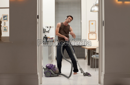 man vacuuming and listening to music