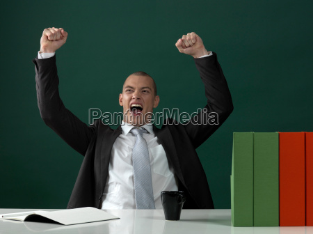business man cheering by office table