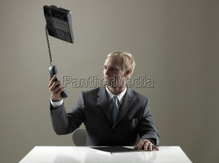business man holding phone in mid