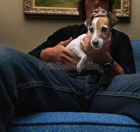 man holding dog wearing tiara