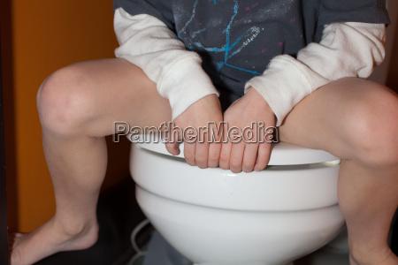 boy sitting on toilet