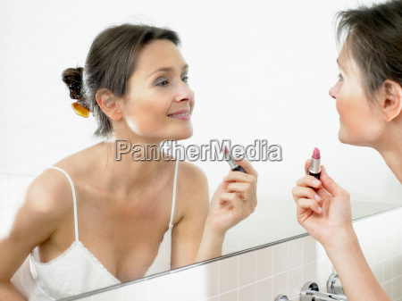 woman in bathroom applying makeup