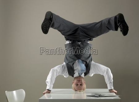 business man standing on head on