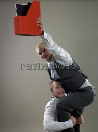 geschaeftsleute die papierhalter platzieren