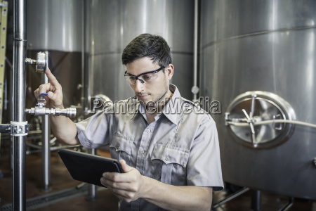 young man in brewery holding digital