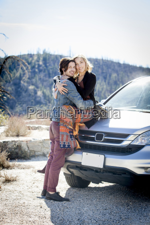 young couple on car bonnet hugging