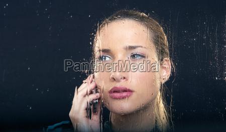 frau am regnerischen fenster mit telefon