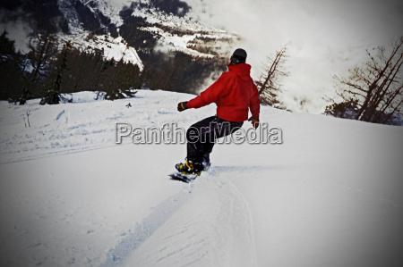 maennlich reiten snowboard rueckansicht